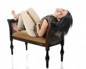 A beautiful teen girl  reclined on a padded bench, looking back at the viewer with her head drapped over the edge.  On a white background.