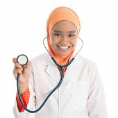 Young Muslim female doctor portrait, holding stethoscope standing isolated on white background.