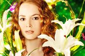 Beautiful gentle girl with red hair among the flowers.