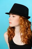 Portrait of a pretty red-haired girl in a hat. Studio shot.