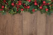 Christmas background border with red bell baubles, fir, holly, ivy, mistletoe and cedar cypress with pine cones over old oak.