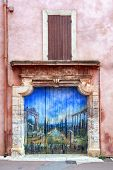 ROUSSILLON, FRANCE - June 17:  Doorway in ancient village of Roussillon, Provence, France, with painting of Roman garden, June 17, 2014.  Roussillon is renowned for its red ochre.