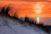 Orange sunset with dune and sea