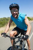 Smiling cyclist riding on the open road on a sunny day