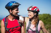 Active couple cycling in the countryside smiling at each other on a sunny day