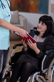 Nurse Giving Book To Disabled Woman