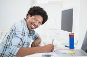 Young designer working at his desk smiling at camera in his office