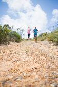 Fit couple jogging down mountain trail on a sunny day