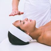 Peaceful brunette getting reiki therapy in the health spa
