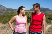 Active couple standing on country terrain smiling at each other on a sunny day