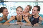 Female fitness class smiling at camera in swimming pool at the leisure centre
