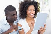 Attractive couple using tablet together on sofa to shop online at home in the living room