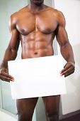 Mid section of a shirtless muscular man holding blank board