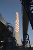 Low angle view of checkered smokestack of oil fired power station