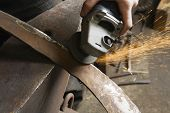Blacksmith using angle grinder on edge of metal tool in workshop