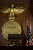 Closeup of judge's seat; bird; gavel and American flag in court room