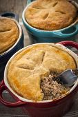 Closeup of three homemade gourmet meat pies with fork showing ground beef filling