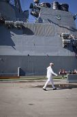 STATEN ISLAND, NY - MAY 25, 2014: A member of the U.S. Navy walks past the hull of the guided-missile destroyer USS Cole (DDG 067) moored at Sullivans Piers for Fleet Week NY.