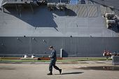 STATEN ISLAND, NY - MAY 25, 2014: A member of the U.S. Navy walks past the hull of the guided-missil