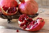 Red Pomegranates On A Plate On Old Wooden Table