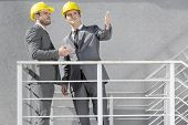 Two young businessmen in hard hats discussing on stairway