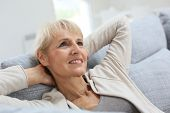 Senior woman relaxing in sofa and looking away