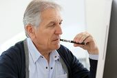 Senior man smoking with e-cigarette at work