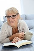Senior woman reading book and relaxing in sofa