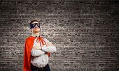 Young man wearing superman mask and cape