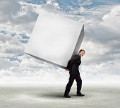 Young businessman carrying white blank cube. Place for text