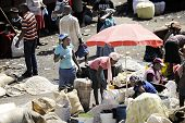 SAINT MARC, HAITI: FEBRUARY 12, 2014  -- Buying and selling under a shade umbrella.