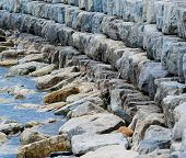 Curving Breakwall Of Stacked Stones.