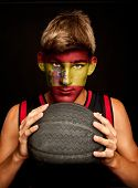 portrait of basketball player with spanish flag painted on his face