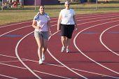Two Women Walking A Track