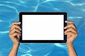 Woman hand holding tablet computer in the pool