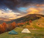 Autumn Landscape with two tents in the mountains. Beautiful night on the campsite