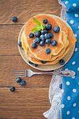 Stack of pancakes with fresh blueberry on wooden background.