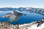 picture of early spring  - Clear blue water of Crater Lake National Park in Oregon during early spring with some snow left from winter - JPG