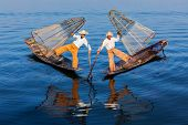 Myanmar travel attraction landmark - Traditional Burmese fishermen balancing with fishing net at Inl