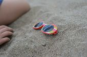 Striped sunglasses in the sand