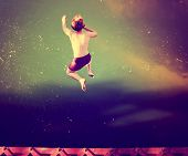 a boy jumping of an old train trestle bridge into a river done with a retro vintage instagram filte