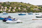 stock photo of ski boat  - Small boats and jet skis anchored by a tropical luxury resort - JPG