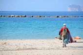 picture of peddlers  - seller walking on the beach in Alghero shore - JPG