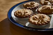 Plate of mince pies shot against the light on a wooden table