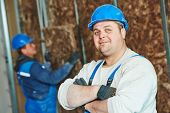 cheerful plasterer worker at a indoors wall insulation works