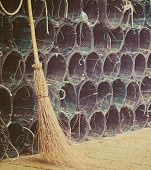 picture of fishnet  - close up of a wicked broom by a group of fishnets in vintage tone - JPG