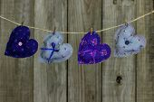 Floral fabric hearts hanging on clothesline by shabby wood background