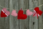 Red fabric hearts hanging on clothesline by rustic wooden background