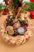 Christmas Decoration With Wicker Basket With Straw And Colored Nuts Inside