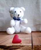 Heart and teddy bear on a wooden surface